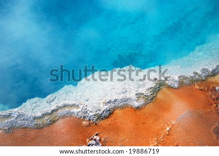 Beautiful detail of a hotspring geyser pool showing multiple vibrants colors