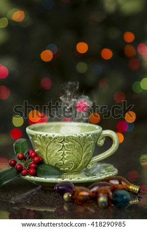 Beautiful detailed green cup with steam rising and Christmas lights and decorations - stock photo