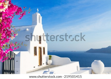 beautiful details of Santorini island - typical house with white walls, pink flowers  and blue sea Greece - stock photo