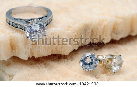 Beautiful diamond engagement ring and diamond stud earrings on coral - stock photo