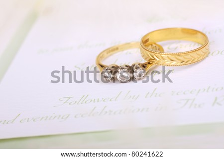 Beautiful diamond engagement ring with wedding band and wedding invitation