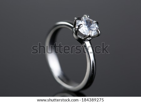 Beautiful diamond ring on gray background - stock photo