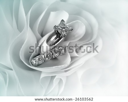 Beautiful diamond wedding ring set displayed in the folds of the fabric of a wedding gown. Space for copy. - stock photo