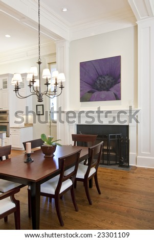 beautiful diningroom with fireplace looking out to kitchen - stock photo
