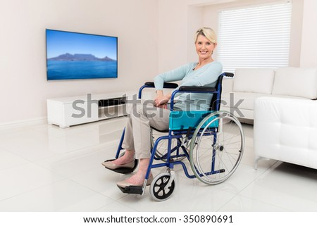 beautiful disabled middle aged woman sitting in living room - stock photo