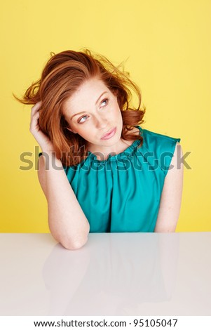Beautiful distracted woman with dishevelled hair seated at a table looking up at the ceiling - stock photo
