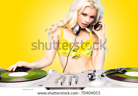 Beautiful DJ girl on decks on the party,blonde model on aqua blue background - stock photo