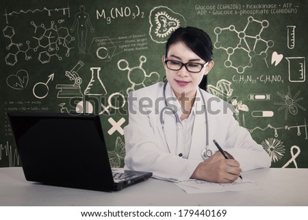 Beautiful doctor is writing prescription at the laboratory