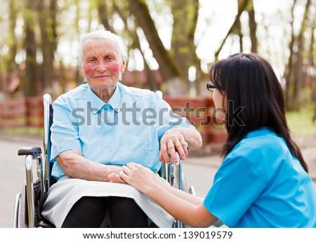 Beautiful doctor, nurse in blue coat walking a kind elderly lady in wheelchair in park. - stock photo