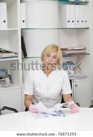 Beautiful doctor or nurse at the table - stock photo