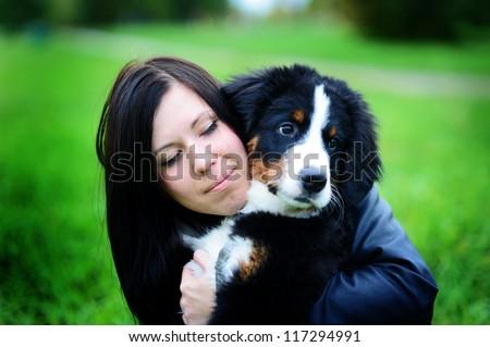 Beautiful dog portrait. Bernese Mountain puppy (Berner Sennenhund) with a beautiful girl on the nature - stock photo