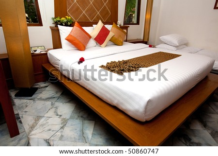 Beautiful double bed in traditional Thai setting - stock photo