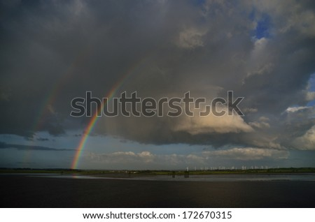 beautiful double rainbow with many windmills at sea
