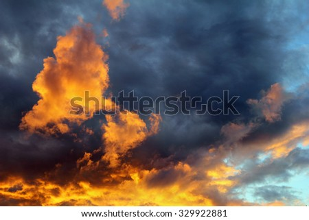 Beautiful dramatic cloudscape with yellow and blue cirrus clouds looks like fire in light of the of the rising sun in Moscow region, Russia - stock photo