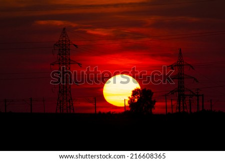 Beautiful, dramatic, colorful clouds and sky at sunset. Electrical wires and stakes and water reflexions. Image has grain texture seen at its maximum size