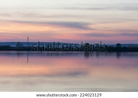 Beautiful, dramatic, colorful clouds and sky at sunset. Trees silhouettes and water reflexions. Image has grain texture seen at its maximum size  - stock photo