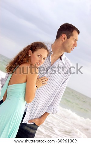 Beautiful dramatic image of young couple on the sea shore, he is turned profile, she is looking at the viewer, shot at an angle - stock photo