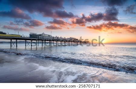 Beautiful dramatic sunrise at Paignton pier in Devon - stock photo
