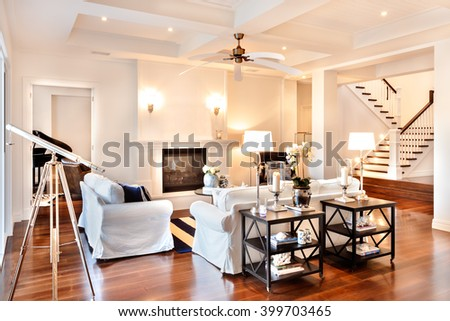 Beautiful drawing room with glossy wooden floor and telescope at the window and white sofa - stock photo