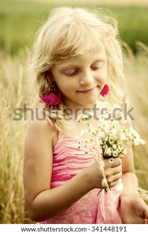 beautiful dreamlike little girl with long blond hair and bunch of flowers in the meadow portrait desaturated effect - stock photo