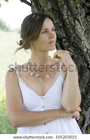 Beautiful, dreamy woman wearing a daisy chain necklace - stock photo