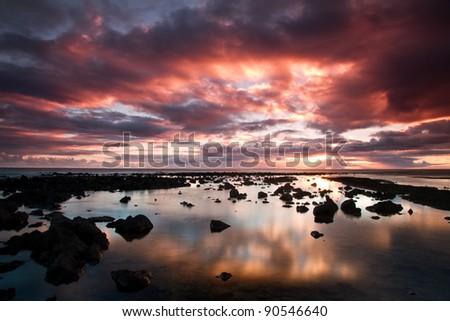Beautiful dusk scene in Kauai, Hawaii. With scattered lava rocks and  dramatic cloudy sky - stock photo