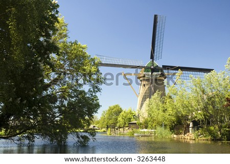 Beautiful dutch windmill in front of a river. Taken with polarisation filter on a sunny day.