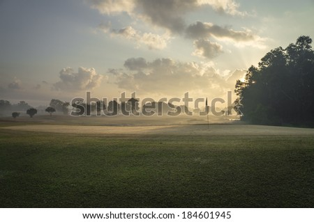 Beautiful early morning golf course in the sunrise - stock photo