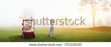 Beautiful early morning golf game at the course in the sunrise and panoramic view - stock photo