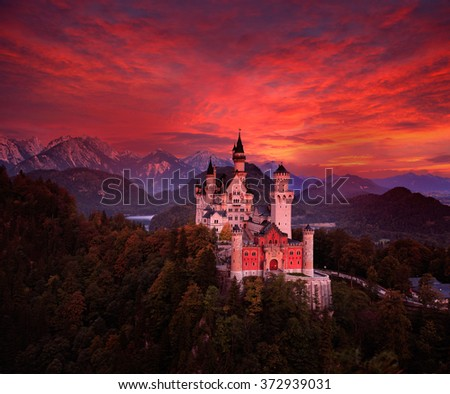 Beautiful early morning view of the Neuschwanstein fairy tale castle, bloody dark sky with autumn colours in the trees during sunrise, twilight, end of night, Bavarian Alps, Bavaria, Germany - stock photo