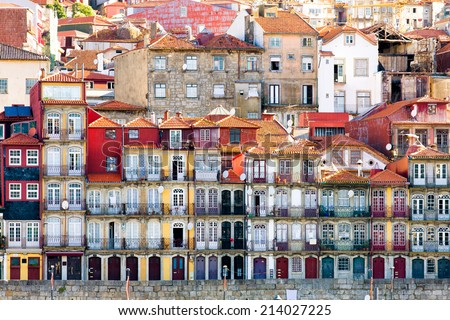 Beautiful early sunlight shedding light on the traditional quaint houses in the old, vintage and touristic ribeira district of Porto, Portugal - stock photo