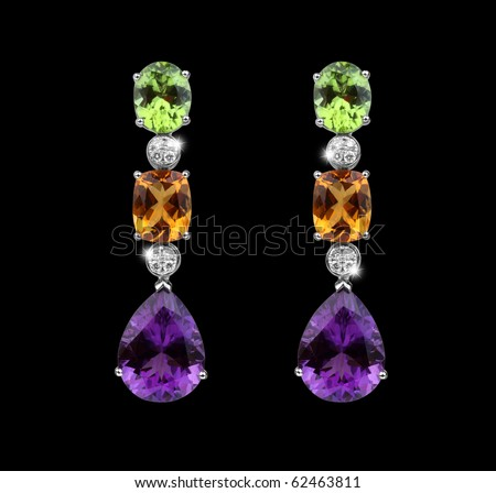 Beautiful Earrings with colorful gems in black background - stock photo