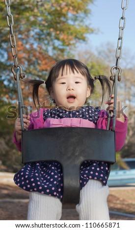 Beautiful East Asian Toddler Girl Swinging in Swing - stock photo