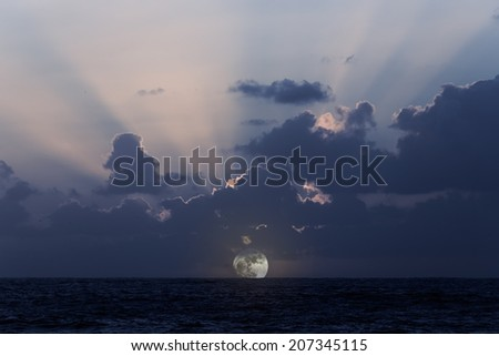 Beautiful east coast moonrise with moonbeams through the clouds - stock photo