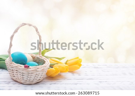 Beautiful Easter eggs in a basket. Delicate yellow spring tulips. Spring Easter holidays. Wooden board rustic - stock photo