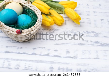 Beautiful Easter eggs in a basket. Delicate yellow spring tulips. Spring Easter holidays. Wooden board rustic