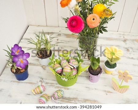 Beautiful easter table decoration with painted eggs, a bouquet of flowers and selfmade fabric flowers in pastel colors