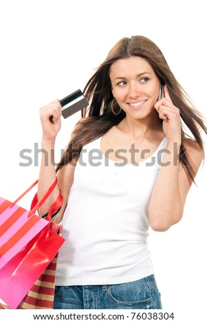 Beautiful ecstatic woman holding shopping bags and credit gift-card in hand, talking by cell phone mobile on a white background - stock photo