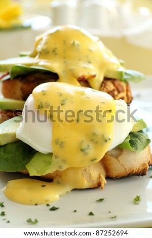 Beautiful eggs benedict with bacon and a rich hollandaise sauce on tiger crust bread. - stock photo