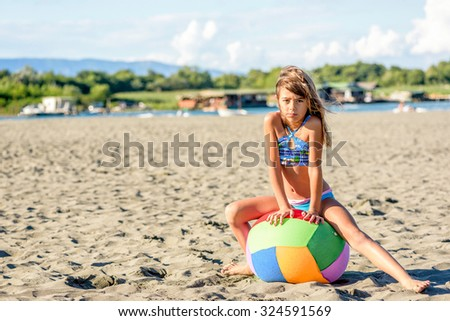 Beautiful eight year old girl playing with the ball on the beach - stock photo