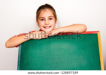 Beautiful eight year old girl with blank chalkboard - stock photo