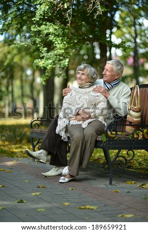 Beautiful elder couple sitting in the park in September