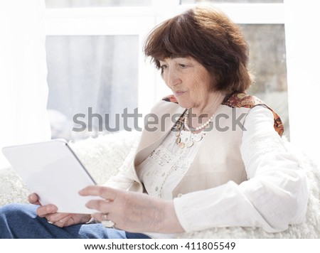 beautiful elderly Caucasian woman sits in armchair and looking at the tablet koipyuter. Horizontal color image. Light background - stock photo