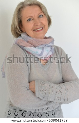 Beautiful elderly lady with a vivacious smile standing with her arms folded grinning happily at the camera