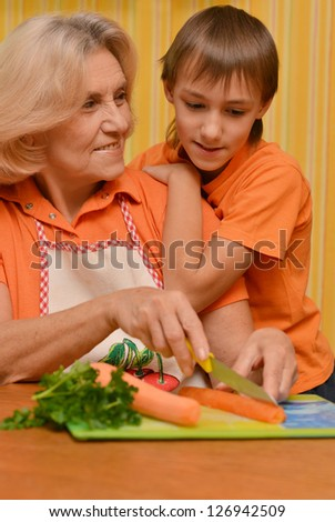 beautiful elderly woman and a boy in the orange in the kitchen - stock photo