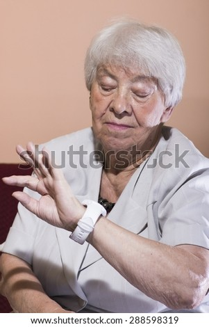 Beautiful elderly woman checking the time looking at her wrist watch as she relaxes on a sofa in her living room - stock photo