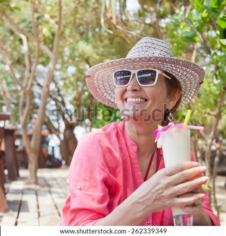 beautiful elderly woman in a hat with a cocktail in hand. Summer, vacation, holiday, active retired people - stock photo