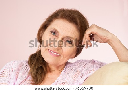 beautiful elderly woman on a pink background