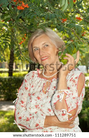 Beautiful elderly woman went for a walk in the garden