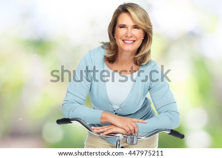 Beautiful elderly woman with bicycle. - stock photo